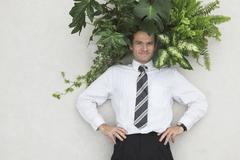 Businessman with Foliage Plants, hands on hips, smiling, portrait, elevated view - stock photo