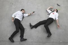 Two businessmen duelling with weapons, portrait, elevated view Stock Photos