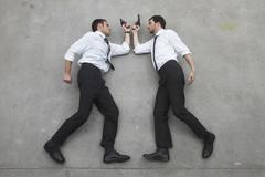 Two businessmen duelling with weapons, portrait, elevated view - stock photo