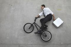 Businessman riding bicycle holding suitcase, elevated view Stock Photos