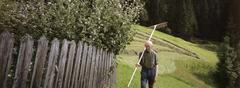 Senior man standing in garden with rake over shoulder Stock Photos