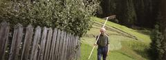 Senior man standing in garden with rake over shoulder - stock photo