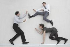 Three business people fighting, elevated view Stock Photos