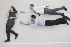 Businesswoman standing, businessmen flying in superman pose, side view Stock Photos