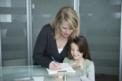 Germany, Bavaria, Landsberg, Mother and daughter (8-9), Mother filling out form Stock Photos