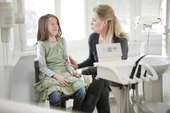 Germany, Bavaria, Landsberg, Mother comforting daughter (8-9) in dental surgery - stock photo