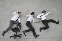 Three businessmen cheering, elevated view Stock Photos