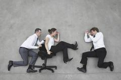 Three business people, business man pushing businesswoman in office chair, side Stock Photos