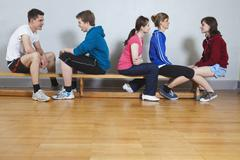 Germany, Berlin, Young and teenage people sitting in school gym Stock Photos