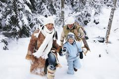 Austria, Salzburger Land, boy (6-7) with parents walking in snow - stock photo