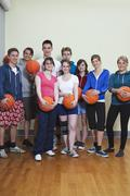 Germany, Berlin, People standing and holding basketball, portrait Stock Photos
