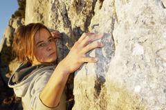 Germany, bavaria, young woman climbing on rock Stock Photos