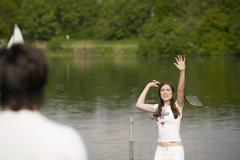 young couple playing badminton, focus on woman - stock photo