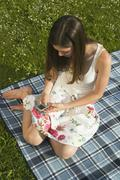 Young woman on picnic blanket, using handy, elevated view Stock Photos