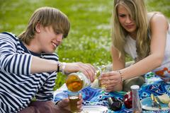 young couple in meadow, man pouring juice - stock photo