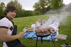 young man grilling young women in background - stock photo
