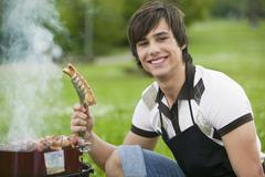 Stock Photo of young man holding grilled sausage, smiling, close-up