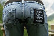 Stock Photo of Back view of woman in jeans  with Anti Nazi applique