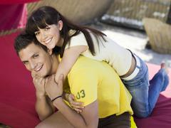 Stock Photo of young woman embracing young man, smiling