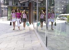 Teenage girls (16-17) walking with shopping bag Stock Photos