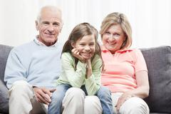 Granddaughter (6-7) sitting on lap of grandparents with head in hand, smiling, Stock Photos