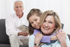 Granddaughter (6-7) hugging grandmother with grandfather in background - stock photo