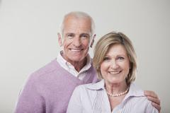 Stock Photo of Senior couple against gray background, smiling, portrait