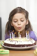 Girl (6-7) blowing out candles on birthday cake Stock Photos