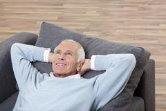 Man with head in hand lying on couch, smiling - stock photo