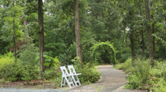 Stone path white chairs archway garden Stock Footage