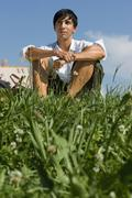 Stock Photo of young man sitting in meadow