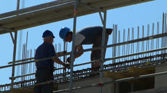 Construction worker bending over metal steel framwork structure Stock Footage