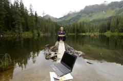 Stock Photo of businesswoman sitting at lake laptop in foreground