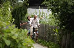 Stock Photo of couple riding bicycle, smiling
