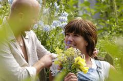 Couple in garden with woman holding bunch of flowers Stock Photos