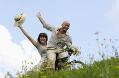 Stock Photo of couple riding bicycle in meadow