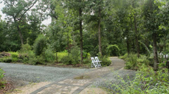 Stone path archway garden white chairs Stock Footage