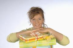 Young woman smiling with head in hand on gift packages, portrait - stock photo