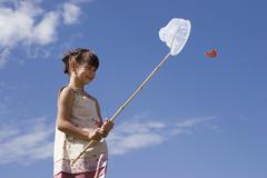 girl (7-9) holding net, trying to catch butterfly - stock photo