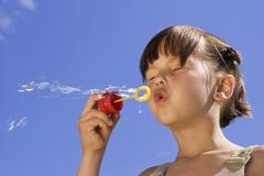 girl (7-9) blowing soap bubbles, eyes closed, close-up - stock photo