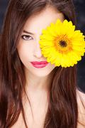 Yellow daisy over woman's eye Stock Photos