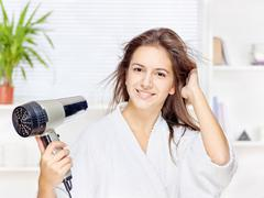 Woman drying hair at home Stock Photos