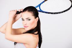 Pretty woman with tennis racket Stock Photos
