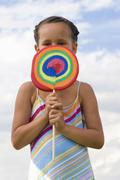 Stock Photo of girl (7-9) holding giant lollipop in front of face, close-up, portrait