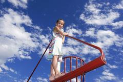 Girl (7-9) climbing on jungle gym Kuvituskuvat