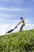 father swinging daughter (7-9) in meadow, side view - stock photo