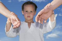 Stock Photo of daughter (7-9) holding hands of parents, close-up