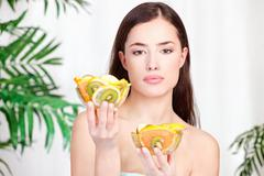 Stock Photo of woman holding bowls full of fruit