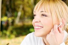 woman in the park with earphones - stock photo