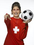 Stock Photo of Woman football fan with Swiss flag painted on face, holding football